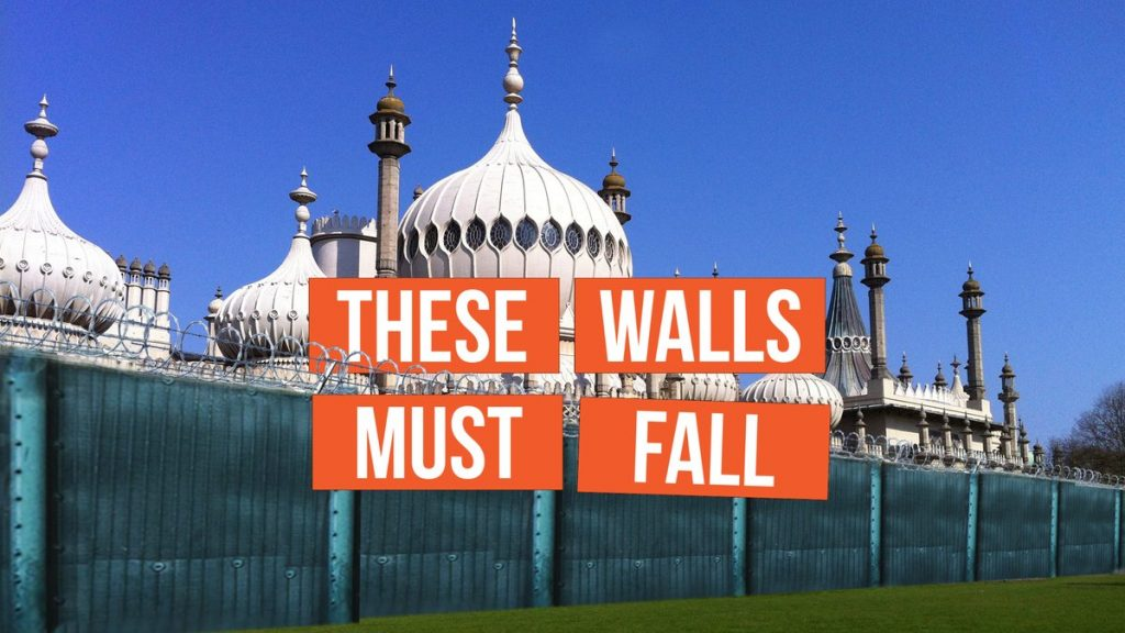Brighton Pavillion surrounded by a fence and razor wire, with the slogan These Walls Must Fall