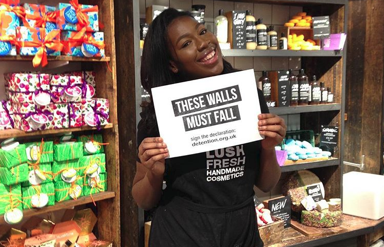 Lush worker with These Walls Must Fall sign