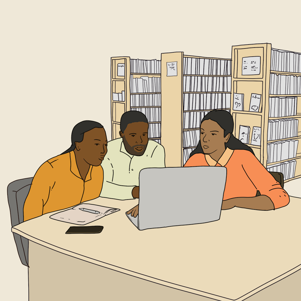 three people sitting together at a laptop, with library book stacks behind them