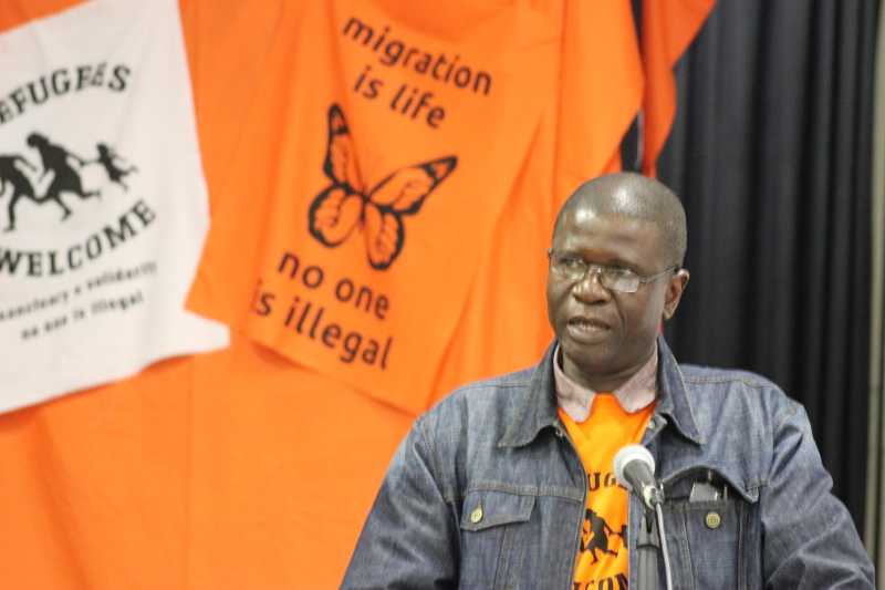 """a campaigner speaking through a microphone with """"Migration is life"""" and """"no one is illegal"""" banners behind him"""